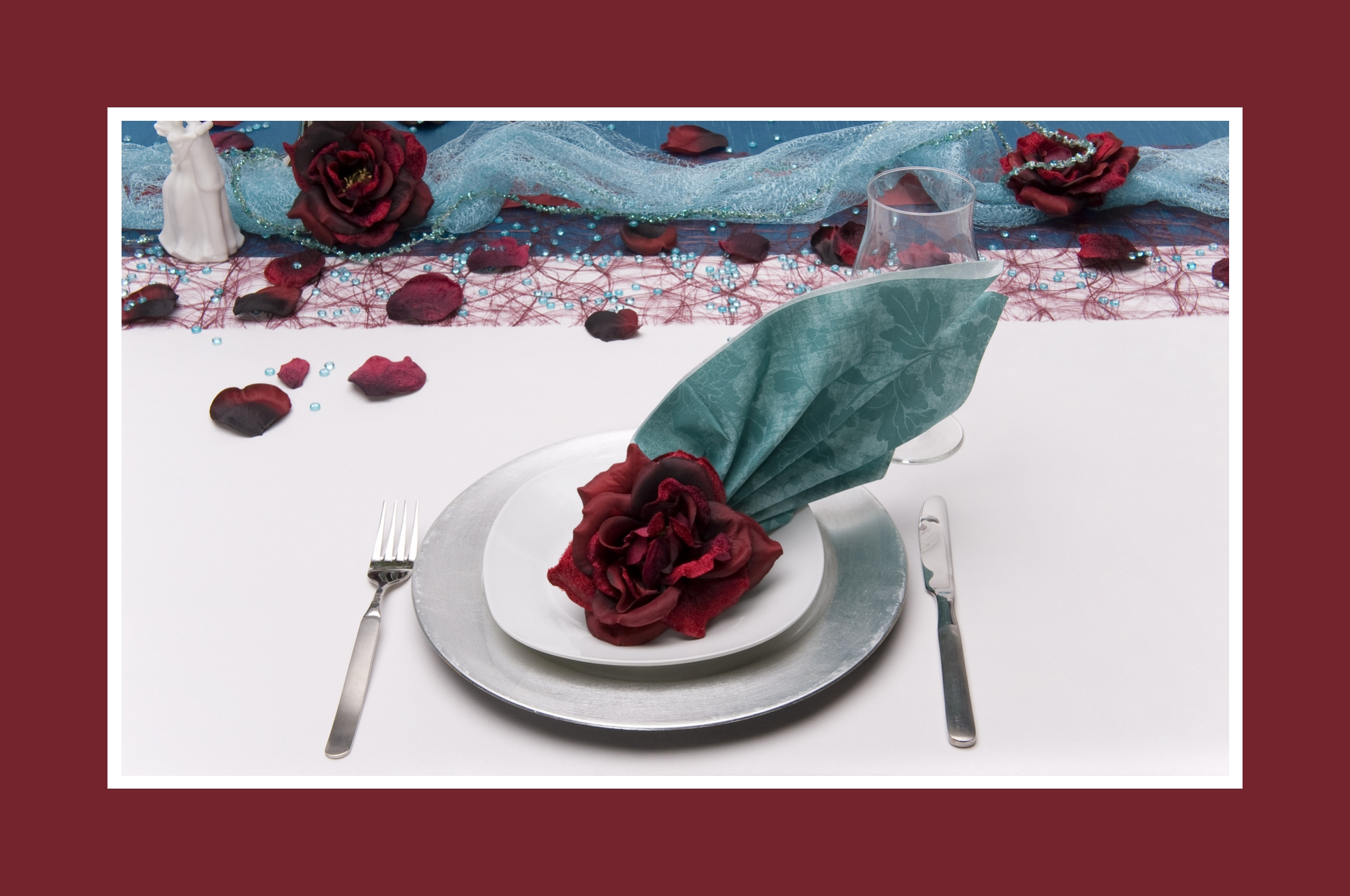 Blaue Serviette und burgunderrote Rose