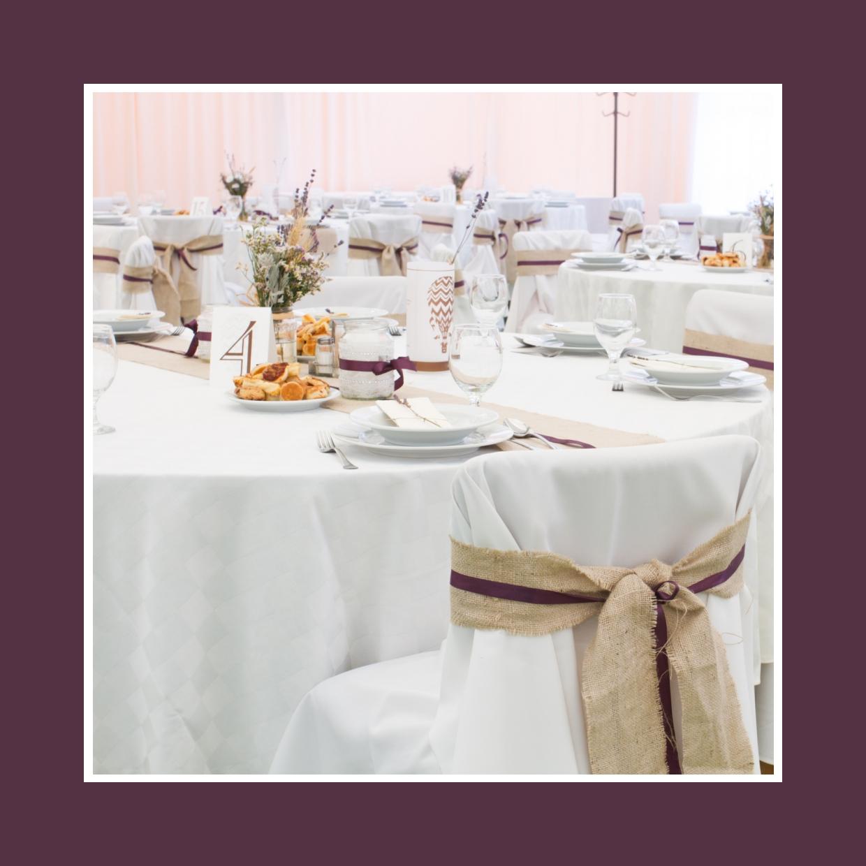 Schleifen auf Stühlen und Tischläufer aus Leinen - alles schön mit lila Bändern verziert