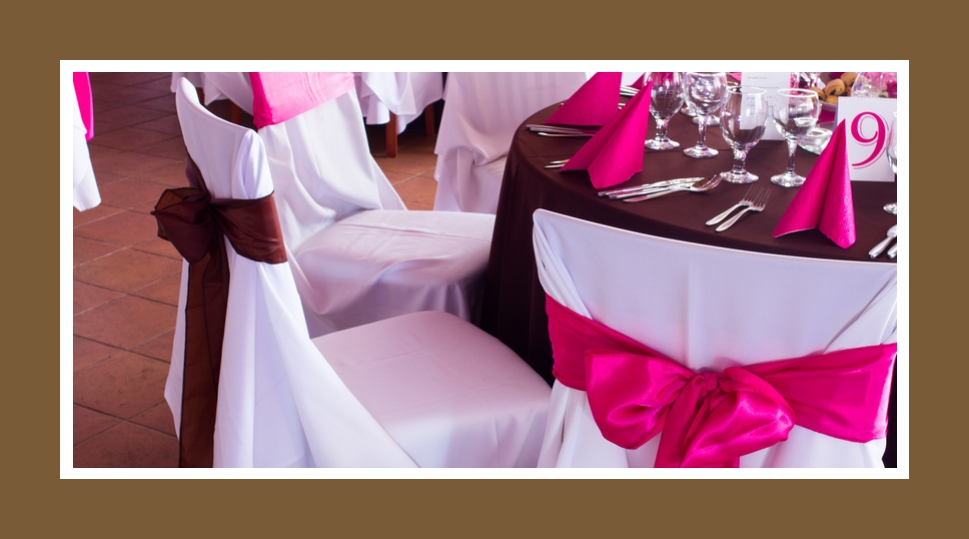 Verschiedenfarbige Schleifen aus pinkem oder marsalafarbenen Satin auf weißen Stuhlhussen