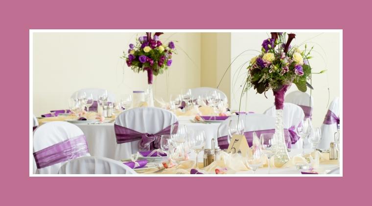 Blumengestecke in hohen Vasen als Tischdeko