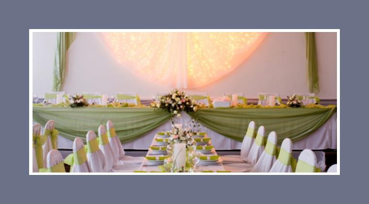 Hochzeitsdeko mit Lichterketten hinter dem Brauttisch
