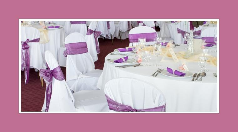 Weiße Tischdecken und Stuhlhussen mit purpurfarbenen Servietten und Schleifen