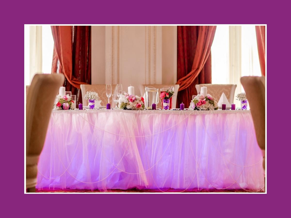 Luftige Deko vom Brautpaartisch mit Ketten und Lichtern