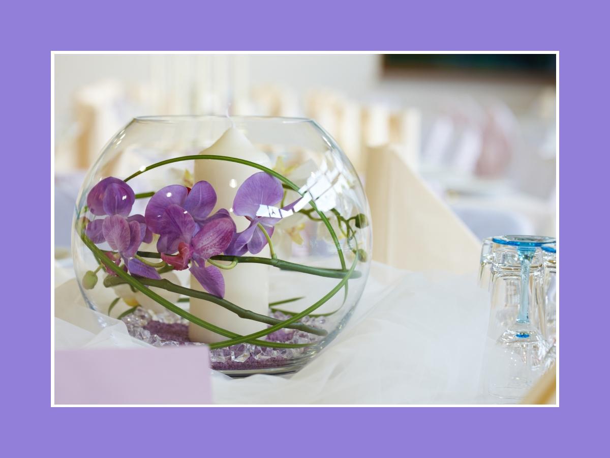 Orchideen und Kerzen in runder Vase
